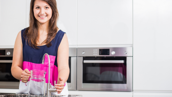 Smiling woman standing at a faucet about to pour water into a glass pitcher